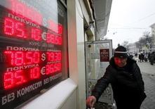 Мужчина тушит сигарету у вывески пункта обмена валюты в Москве 18 января 2016 года. Рубль в понедельник достиг новых 13-месячных минимумов, копируя тенденции рынка нефти, упавшего до значений осени 2003 года на фоне ожиданий роста экспорта из Ирана, с которого в выходные были сняты экономические санкции. REUTERS/Sergei Karpukhin