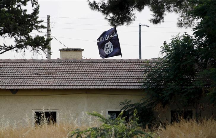An Islamic State flag flies over the custom office of Syria's Jarablus border gate as it is pictured from the Turkish town of Karkamis, in Gaziantep province, Turkey August 1, 2015.  REUTERS/Murad Sezer/Files