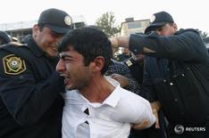 Полиция задерживает протестующего в Баку 12 октября 2013 года. Нефтедоллары и хорошо оснащенные силовики долго обеспечивали тишину в азербайджанском городке, но выросшие в последние месяцы цены вывели на улицы недовольных. REUTERS/David Mdzinarishvili