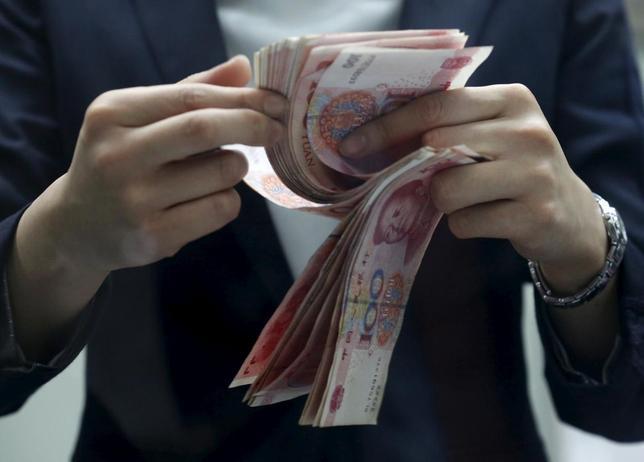 1月18日、中国の12月の外貨取引は6290億元相当の売り越しとなった。写真は人民元紙幣を数える北京の銀行員。4日撮影(2016年 ロイター/Kim Kyung-Hoon)