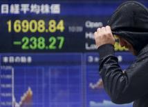 Мужчина у брокерской конторы в Токио, на экране которой отражено значение индекса Nikkei. Токио, 18 января 2016 года. Японский фондовый рынок вырос во вторник впервые за четыре дня, так как инвесторы покупали подешевевшие в последнее время акции, а данные о росте ВВП Китая совпали с прогнозами. REUTERS/Yuya Shino