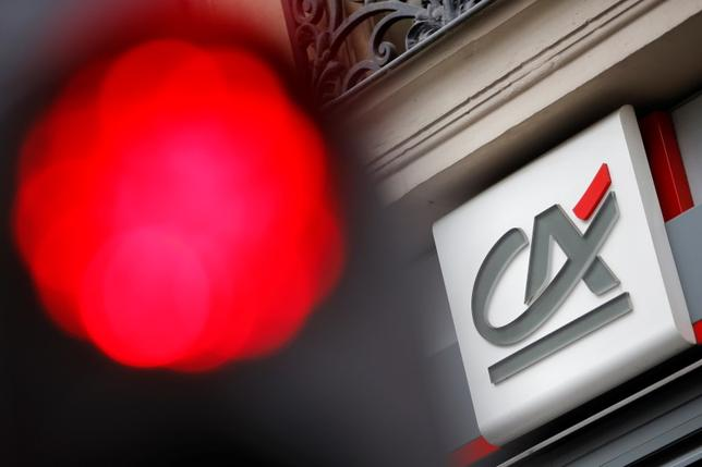 A traffic light shines red near a Credit Agricole logo, pictured on a bank branch in Paris, France, August 4, 2015. REUTERS/Stephane Mahe