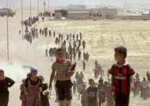 """Езиды идут в сторону сирийской границы из иракского города Синджар, на который напали боевики ИГ. 10 августа 2014 года. Около 3.500 человек, в основном женщины и дети, предположительно находятся в рабстве у боевиков """"Исламского государства"""" в Ираке, подвергаясь пыткам и суровым наказаниям, вплоть до публичных казней, сообщила Организация Объединённых Наций. REUTERS/Rodi Said"""