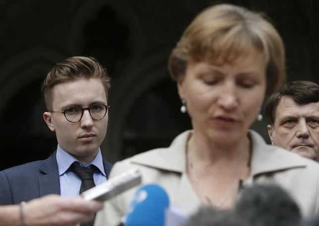Anatoly Litvinenko (L), the son of murdered KGB agent Alexander Litvinenko, listens as his mother Mariana speaks to members of the media as she leaves the High Court in central London, Britain July 31, 2015. REUTERS/Peter Nicholls