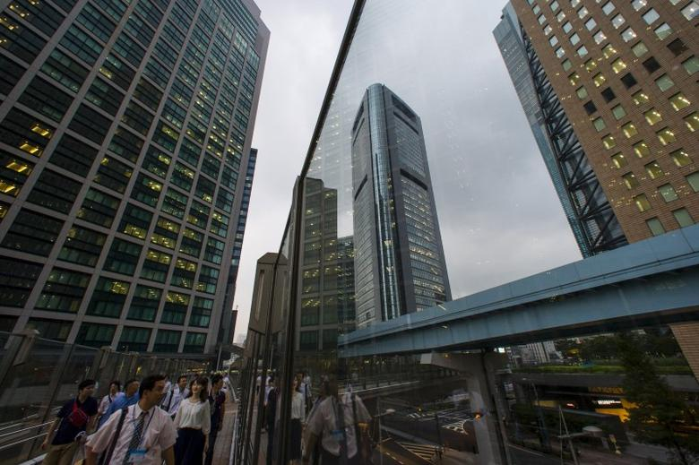 People walk in the shadows of office skyscrapers in a business district in Tokyo August 20, 2015. REUTERS/Thomas Peter