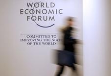 Una persona pasa frente a un anuncio del Foro Económico Mundial de cara al encuentro en Davos, Suiza, ene 18, 2016. Más de un billón de dólares en flujos de inversiones han salido de mercados emergentes en los últimos 18 meses, pero el éxodo podría estar lejos de terminar, dado que economías otrora pujantes parecen estar atrapadas en un débil ciclo de crecimiento e inversiones.  REUTERS/Ruben Sprich