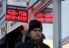 A man walks by a board showing currency exchange rates of the U.S. dollar and euro against the rouble, in central Moscow, Russia, January 11, 2016. REUTERS/Maxim Zmeyev