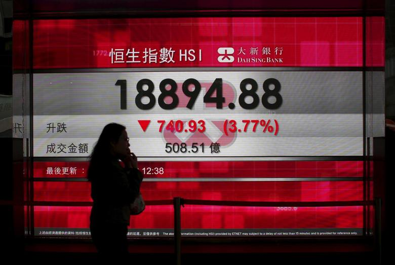 A woman talking on a mobile phone walks past a panel displaying the midday Hang Seng Index in Hong Kong, China January 20, 2016.  REUTERS/Bobby Yip