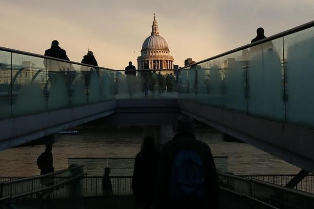 City workers walk towards St Paul's Cathedral as they cross the Millennium footbridge during sunrise in central London, Britain January 14, 2016.  REUTERS/Stefan Wermuth