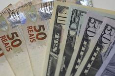 Billetes de 50 reales brasileños junto a dólares estadounidenses. El real brasileño sufría fuertes pérdidas el miércoles tras la apertura de la sesión y traspasó la barrera de 4,10 unidades por dólar, su menor nivel desde fines de septiembre, ya que el nuevo desplome de los precios globales del petróleo exacerbaba la aversión al riesgo de los inversores. REUTERS/Ricardo Moraes