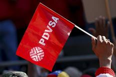 Un trabajador de la petrolera estatal venezolana PDVSA, sostiene una bandera con el logo de la compañía, durante una reunión con el presidente Nicolás Maduro, afuera del Palacio de Miraflores, en Caracas. 12 de enero de 2016. El parlamento en Venezuela, que por primera vez en 16 años está controlado por la oposición, planea investigar la salud financiera de la estatal Petróleos de Venezuela (PDVSA) y los préstamos a cambio de crudo que acordó el gobierno socialista con China, dijo un legislador el martes. REUTERS/Carlos Garcia Rawlins
