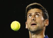 Serbia's Novak Djokovic bounces a ball as he prepares to serve during his second round match against France's Quentin Halys at the Australian Open tennis tournament at Melbourne Park, Australia, January 20, 2016. REUTERS/Thomas Peter