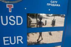 Идущая по улице женщина отражается в электронном табло с курсами валюты в Алма-Ате 20 августа 2015 года. Fitch снизило рейтинги Казкоммерца, сообщив, что крупнейшему банку Казахстана могут потребоваться внешняя поддержка капиталом или реструктуризация долга, чтобы восстановить платежеспособность после резкого падения тенге. REUTERS/Pavel Mikheyev