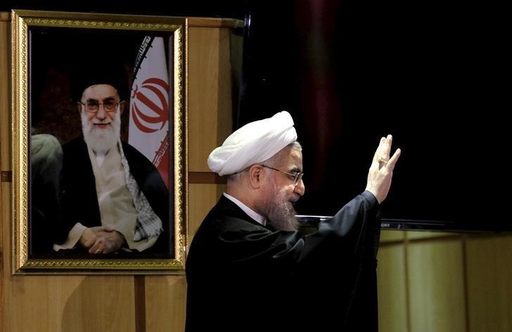 Iranian President Hassan Rouhani waves as he stands next to a portrait of Iran's Supreme Leader Ayatollah Ali Khamenei, after he registered for February's election of the Assembly of Experts, the clerical body that chooses the supreme leader, at Interior Ministry in Tehran December 21, 2015. REUTERS/Raheb Homavandi/TIMA
