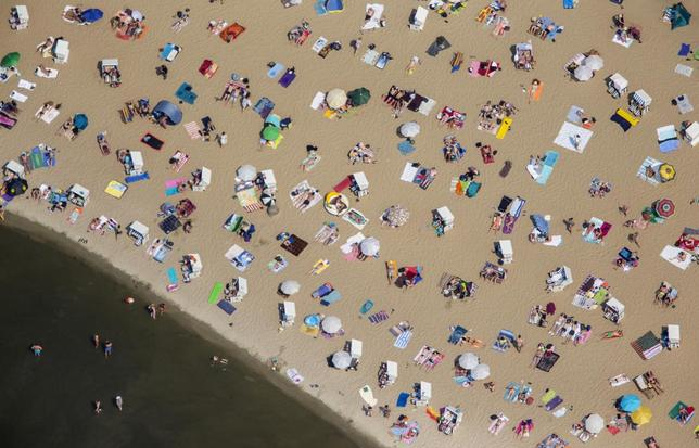 People swim and sunbathe on a hot sunny summer day at the beach of Wannsee near Berlin, Germany, July 4, 2015. REUTERS/Hannibal Hanschke