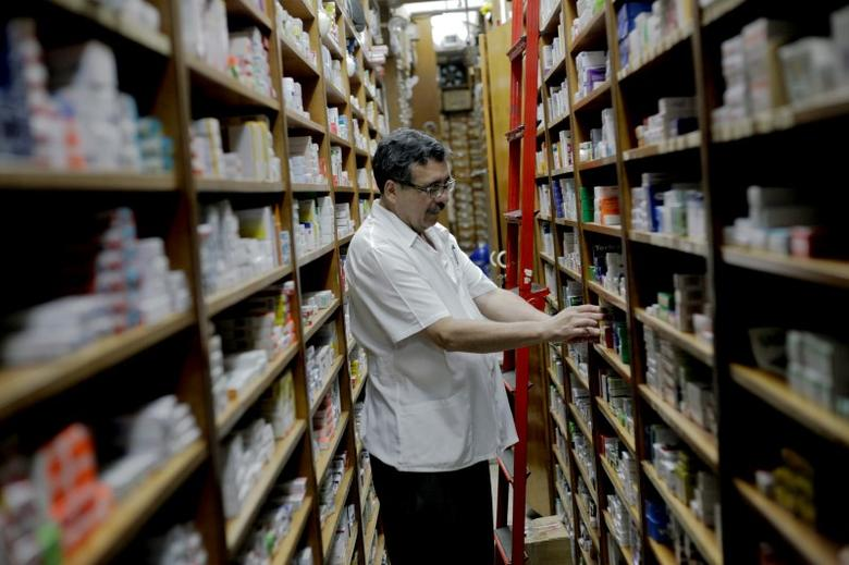 File photo of a pharmacy employee looks at medicine for sale in a drugstore in Caracas January 4, 2011. REUTERS/Gil Montano