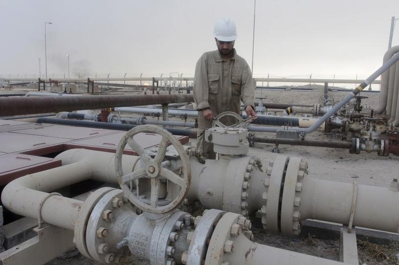 A worker checks the valve of an oil pipe at Rumaila oilfield in Basra, southeast of Baghdad, Iraq June 6, 2015.    REUTERS/Stringer