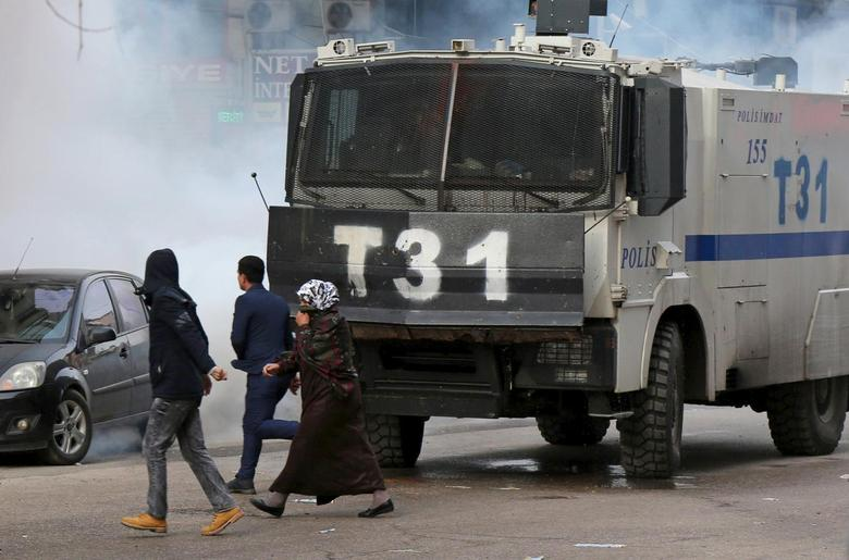 People walk past an armored police vehicle as Turkish riot police use tear gas to disperse Kurdish demonstrators during a protest against a curfew in Sur district and security operations in the region, in the southeastern city of Diyarbakir, Turkey January 17, 2016. REUTERS/Sertac Kayar
