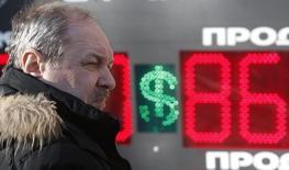 Мужчина на фоне табло с курсами обмена валют в Москве 21 января 2016 года. Рубль остается в существенном минусе вечером четверга, но отскочил с исторического дна в паре с долларом на фоне попыток стабилизации нефтяных котировок, которые тем не менее остаются вблизи многолетних минимумов. REUTERS/Sergei Karpukhin