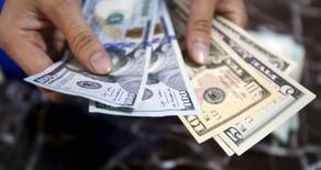 Работник банка считает доллары. Ханой, 12 августа 2015 года. Доллар укрепился к корзине основных валют в пятницу, так как рост ожиданий дальнейшего смягчения денежно-кредитной политики других крупных центробанков перевесил снижающиеся шансы на подъём ставки Федрезервом США. REUTERS/Kham