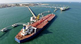 La agencia de calificación Moody's situó a gran parte del sector del gas y el petróleo en revisión a la baja, mientras el hundimiento de más del 70 por ciento de los precios del petróleo en los últimos 18 meses ha arrastrado también a las acciones de las empresas energéticas.  En la imagen, una panorámica de un puerto de importación de crudo en Qingdao, provincia de Shandong, 9 de noviembre de 2008. REUTERS/Stringer