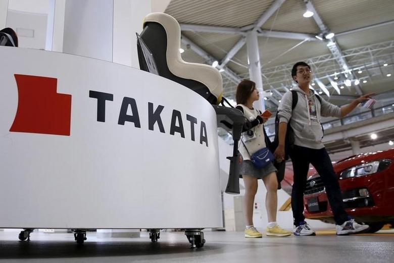 Visitors walk behind a logo of Takata Corp on its display at a showroom for vehicles in Tokyo, Japan, November 6, 2015. REUTERS/Toru Hanai