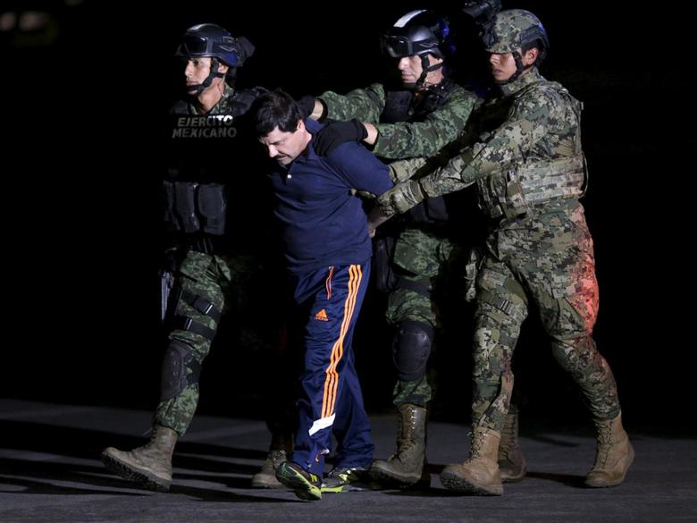 Recaptured drug lord Joaquin ''El Chapo'' Guzman is escorted by soldiers at the hangar belonging to the office of the Attorney General in Mexico City, Mexico January 8, 2016. REUTERS/Henry Romero