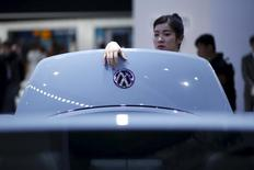 A woman looks a Volkswagen car during a presentation at the 16th Shanghai International Automobile Industry Exhibition in Shanghai, April 21, 2015. REUTERS/Aly Song