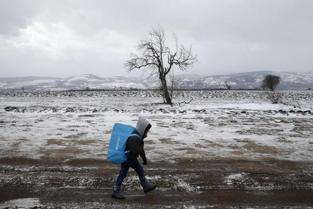 A migrant child walks through a frozen field after crossing the border from Macedonia, near the village of Miratovac, Serbia, January 18, 2016. REUTERS/Marko Djurica