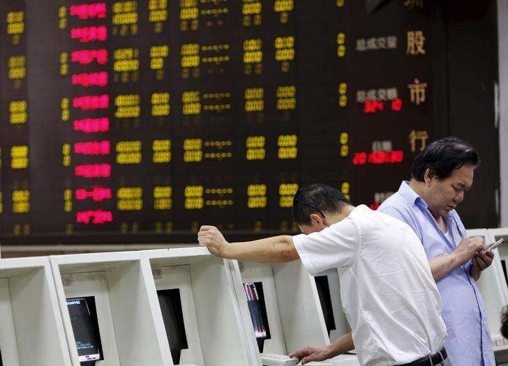 Investors are seen in front of an electronic screen showing stock prices at a brokerage house in Beijing, China, June 30, 2015. REUTERS/Kim Kyung-Hoon