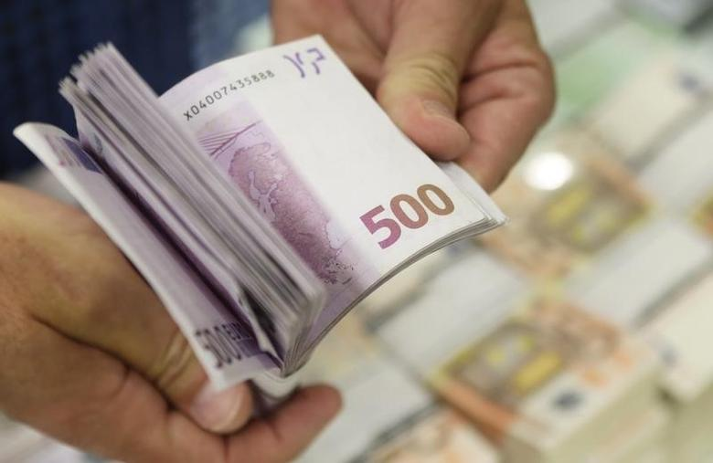 An employee of GSA Austria holds a wad of 500 euro banknotes at the company's headquarters in Vienna in this July 22, 2013 file photo.    REUTERS/Leonhard Foeger/Files