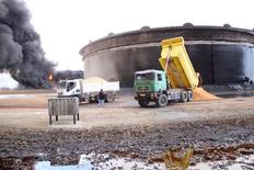 Un tanque de almacenamiento de petróleo quemandose en el puerto de Ras Lanuf, Libia, 23 de enero de 2016. La caída en la producción de petróleo en Libia en los últimos  años como consecuencia de la violencia ha generado pérdidas de ingresos por 68.000 millones de dólares, dijo el lunes el presidente de la estatal National Oil Corp (NOC), Mustafa Sanallah.  REUTERS/Stringer