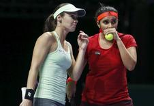 Martina Hingis (L) of Switzerland and Sania Mirza (R) of India talk before a serve to Garbine Muguruza of Spain and compatriot Carla Suarez Navarro during their women's doubles finals tennis match of the WTA Finals at the Singapore Indoor Stadium November 1, 2015. REUTERS/Edgar Su