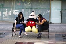 Mujeres revisan sus celulares junto a un peluche de Mickey Mouse, afuera de un centro comercial en Santiago. 10 de diciembre de 2014. Nueve de cada diez chilenos no se van a dormir sin antes revisar sus mensajes y redes sociales, casi dos tercios cree que el teléfono móvil es el aparato más importante de la casa y son las mujeres quienes más lo valoran, según un estudio de una encuestadora y una empresa de servicios de telecomunicaciones. REUTERS/Ivan Alvarado