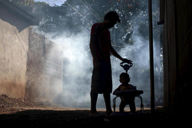 A man and his son stand outside their house while a health ministry worker fumigates in Managua, Nicaragua January 26, 2016. REUTERS/Oswaldo Rivas