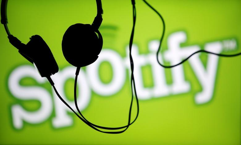 Headsets hang in front of a screen displaying a Spotify logo on it, in Zenica February 20, 2014. REUTERS/Dado Ruvic