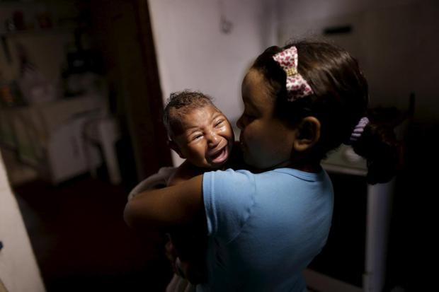 Camile Vitoria embraces her brother Matheus, who has microcephaly, in Recife, Brazil, January 27, 2016.  REUTERS/Ueslei Marcelino