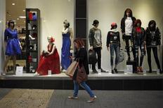 Las ventas minoristas frenaron su ritmo de crecimiento en diciembre aunque encadenaron el decimoséptimo mes de alzas, apoyadas en un mayor consumo de los hogares. En la imagen, una mujer, con bolsas de la compra, mira su móvil mientras pasa junto a una tienda en Málaga, el 27 de noviembre de 2015. REUTERS/Jon Nazca