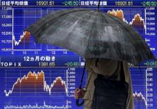 Человек проходит мимо электронного табло с котировками индекса Nikkei average в Токио 18 января 2016 года. Японский индекс Nikkei завершил неспокойные торги четверга снижением из-за волатильности цен на нефть и беспокойств о замедлении темпов роста глобальной экономики, которое продолжает оказывать давление на инвесторов, ожидающих итогов заседания Банка Японии в пятницу. REUTERS/Yuya Shino