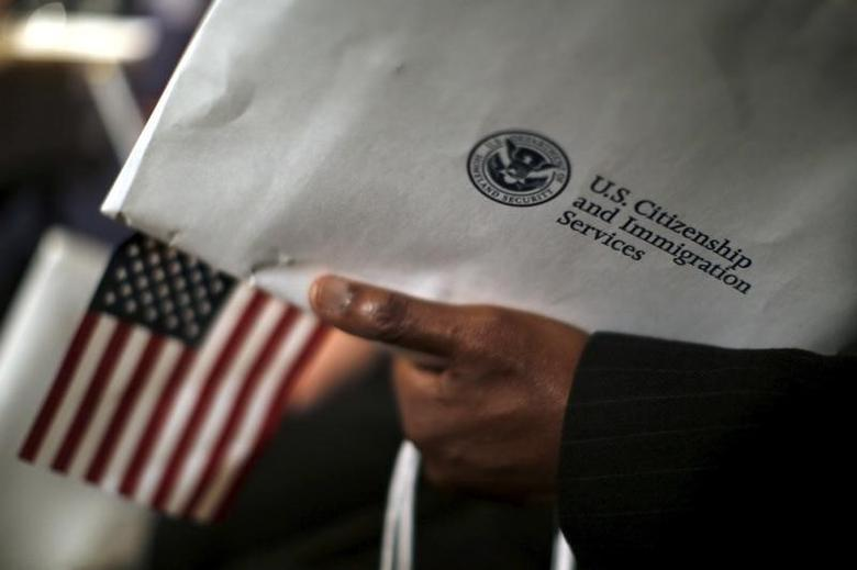 A man holds an envelope from the U.S. Citizenship and Immigrations Service during a naturalization ceremony at the National Archives Museum in Washington December 15, 2015.  REUTERS/Carlos Barria