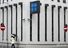 A woman with an umbrella walks past the logo of the Organization of the Petroleum Exporting Countries (OPEC) at the new OPEC headquarters during rainfall in Vienna March 16, 2010. REUTERS/Heinz-Peter Bader