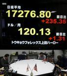 Empleados de una firma de cambio trabajan bajo una pantalla que muestra el índice Nikkei de Japón (arriba) y el tipo de cambio del yen japonés frente al dólar en una sala de operaciones en Tokio, Japón, 29 de enero del 2016. Las bolsas de Asia saltaban y el yen retrocedía después de que el Banco de Japón sorprendió a los mercados el viernes al adoptar unas tasas de interés negativas en su medida más audaz a la fecha para reactivar a la economía. REUTERS/Yuya Shino
