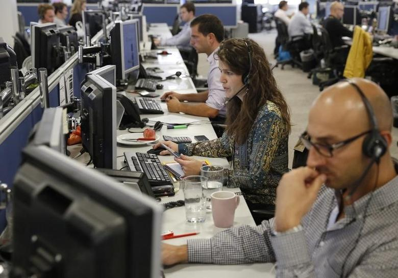Traders sit at their desks at IG Index in London September 9, 2014.    REUTERS/Luke MacGregor