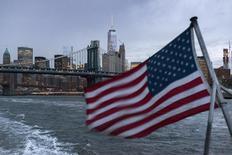 El puente Manhattan se ve en el fondo mientras un barco con una bandera de Estados Unidos cruza el Río Este, en Nueva York. 21 de septiembre de 2015. El crecimiento económico de Estados Unidos se frenó bruscamente en el cuarto trimestre debido a que las empresas incrementaron los esfuerzos para reducir un exceso de inventarios, mientras que la fortaleza del dólar y la debilidad de la demanda global pesaron sobre las exportaciones. REUTERS/Darren Ornitz