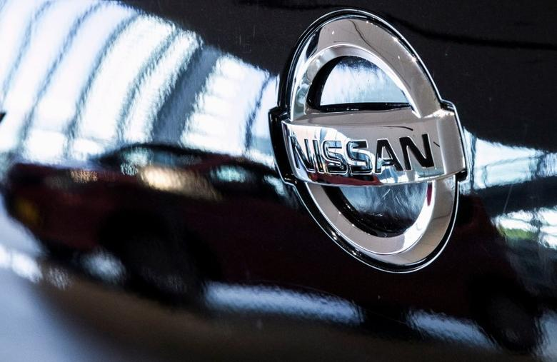 A car is reflected in the bonnet of a Nissan car in the showroom at Nissan's global headquarters in Yokohama south of Tokyo, February 9, 2015. REUTERS/Thomas Peter