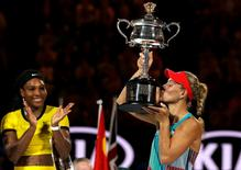 Germany's Angelique Kerber kisses the trophy as Serena Williams of the U.S. claps after Kerber won their final match at the Australian Open tennis tournament at Melbourne Park, Australia, January 30, 2016. REUTERS/Tyrone Siu