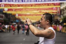 A Chinese tourist with a tattoo of China's late Chairman Mao Zedong takes pictures in Bangkok's Chinatown decorated for the Chinese Lunar New Year February 19, 2015. REUTERS/Damir Sagolj/Files