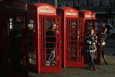 La británica BT Group anunció el lunes su mayor crecimiento de ingresos de los últimos siete años en el último trimestre del año, impulsado por un fuerte consumo en banda ancha lo que sitúa a la compañía en una posición fuerte para incorporar al líder del mercado móvil EE. Gente entra y sale de las cabinas de teléfono tradicionales en el centro de Londres. 15 de enero de 2015.  REUTERS/Luke MacGregor