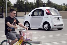 A Google employee on a bicycle acts as a real-life obstacle for a Google self-driving prototype car to react to during a media preview of Google's prototype autonomous vehicles in Mountain View, California September 29, 2015.  REUTERS/Elijah Nouvelage
