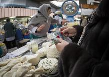 """Женщина считает деньги на базаре в Алма-Ате. 24 января 2015 года. Жители Казахстана, беспокоящиеся о том, что могут потерять работу или оказаться в тюрьме за критику власти, нашли новый способ пожаловаться на экономические трудности: веб-сайт, название которого примерно переводится как """"О Господи"""". REUTERS/Shamil Zhumatov"""